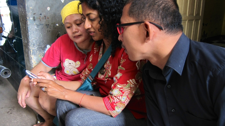 Meena and Alfan discuss AtmaGo with a user in the Halim neighborhood of Jakarta.